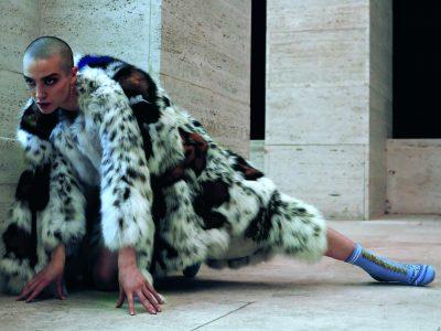 Wadenlanger taillierter Fairy-Lynx-Pelzmantel aus Luchsfell mit weiß-grau geflecktem Gheronato-Zobel-Motiv sowie darüber getragenes Cape aus demselben Pelz und mit Farbeinsätzen in Blau, Rot und Braun Hohe Stiefeletten in Blau mit weißen Streifen und Stickereien sowie goldener Stoffschnürung