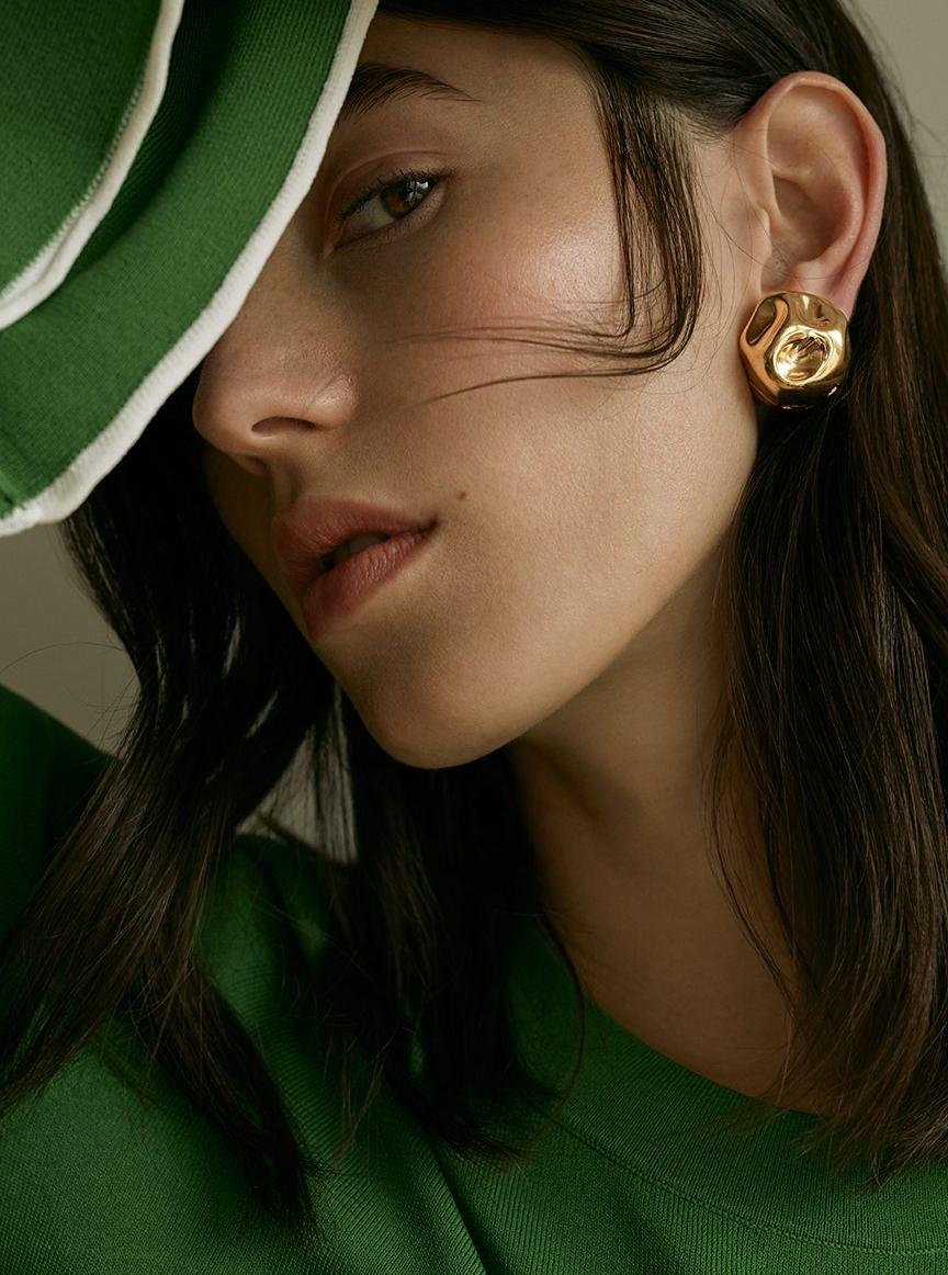 green sweater model brown hair gold earring